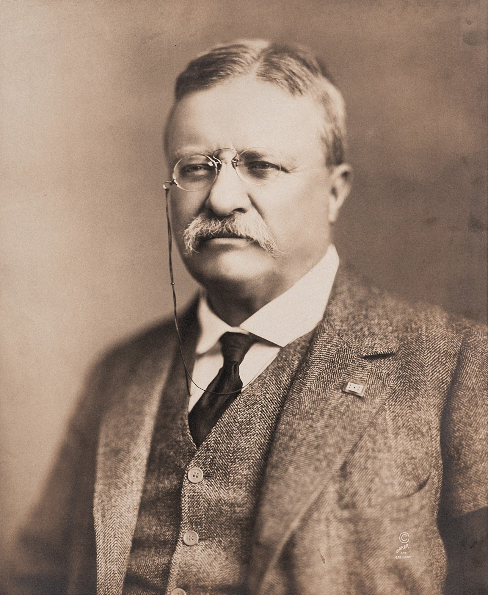 Picture of President Theodore Roosevelt in 1918 in a suit and tie and a monocle.
