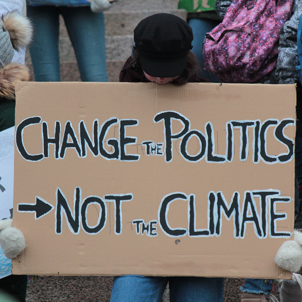 "Image of a climate activist holding a sign that reads ""Change The Politics Not The Climate"""