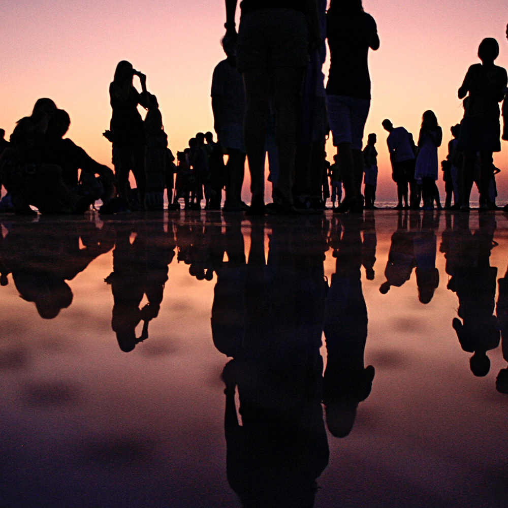 A group of people silhouetted against the sunset they are watching