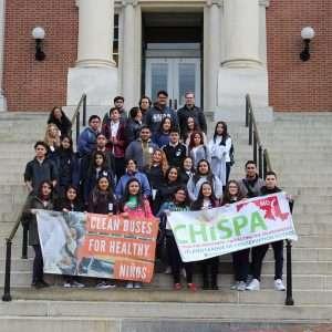Estudiantes de CHISPA para una foto grupal con una pancarta de CHISPA y autobuses limpios para niños saludables